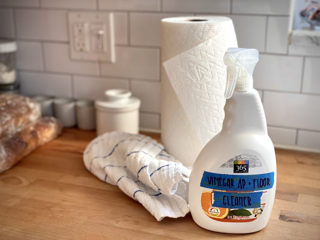 """A white plastic bottle of cleaner sitting in front of a roll of paper towels and a scrunched white and blue striped hand towel. The original label on the plastic bottle has been taped over with two strips of blue painters tape with """"Vinegar AP + Floor Cleaner"""" written on them in black Sharpie."""