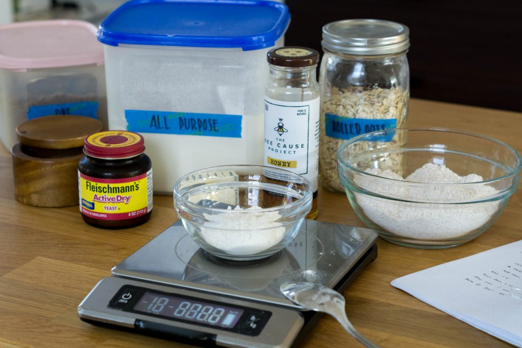 A small bowl of flour on a digital scale. A spoon rests on the bottom corner of the scale. Behind the bowl are arrayed a number of baking ingredients, including honey, rolled oats, all-purpose flour, and instant yeast.