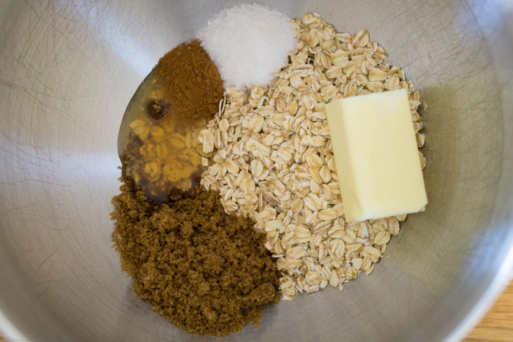 An overhead view of baking ingredients in the bottom of the bowl of a stand mixer. Each ingredient is in separate piles. Going clockwise from the top, there is salt, rolled oats, a chunk of butter, dark brown sugar, honey, and cinnamon.