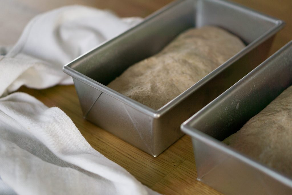 Two unrisen loaves of bread in grey metal loaf pans. A white towel is crumpled up next to them.