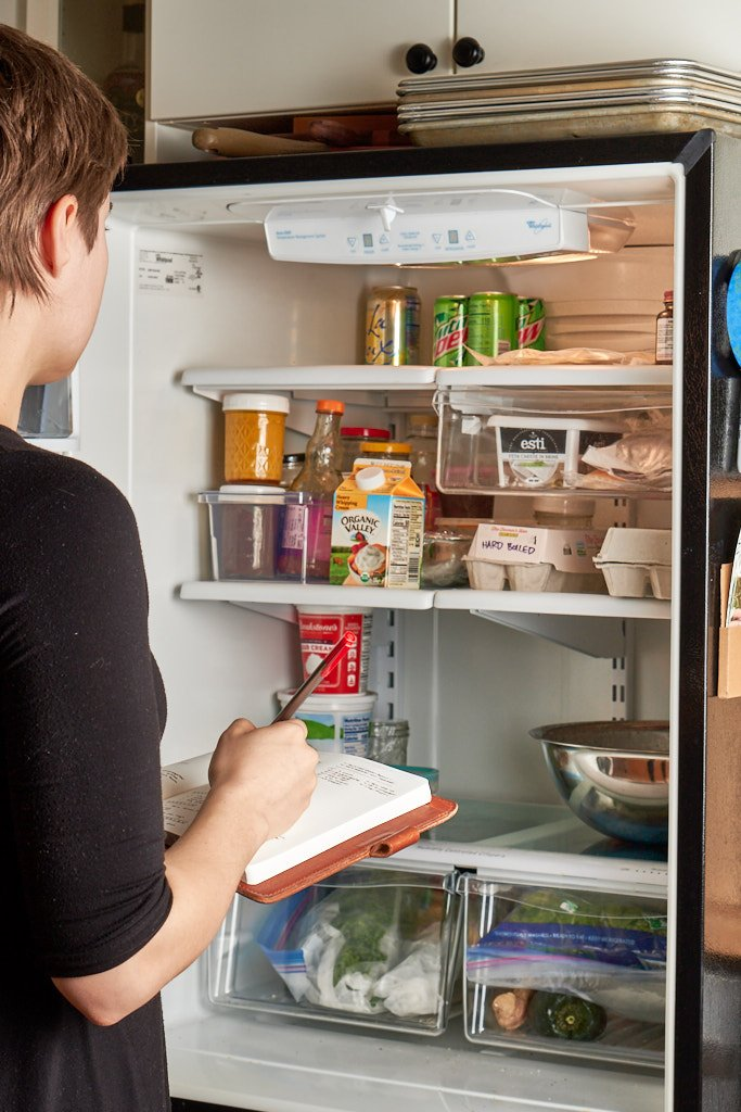 A woman stands in front of a refrigerator with the door open. She's holding a notebook open and crossing items off in red pen.