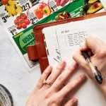 "A notebook sits on top of a grocery store sales flyer. The title of the page is obscured by two hands. One is writing items into a list called ""menu ideas"""