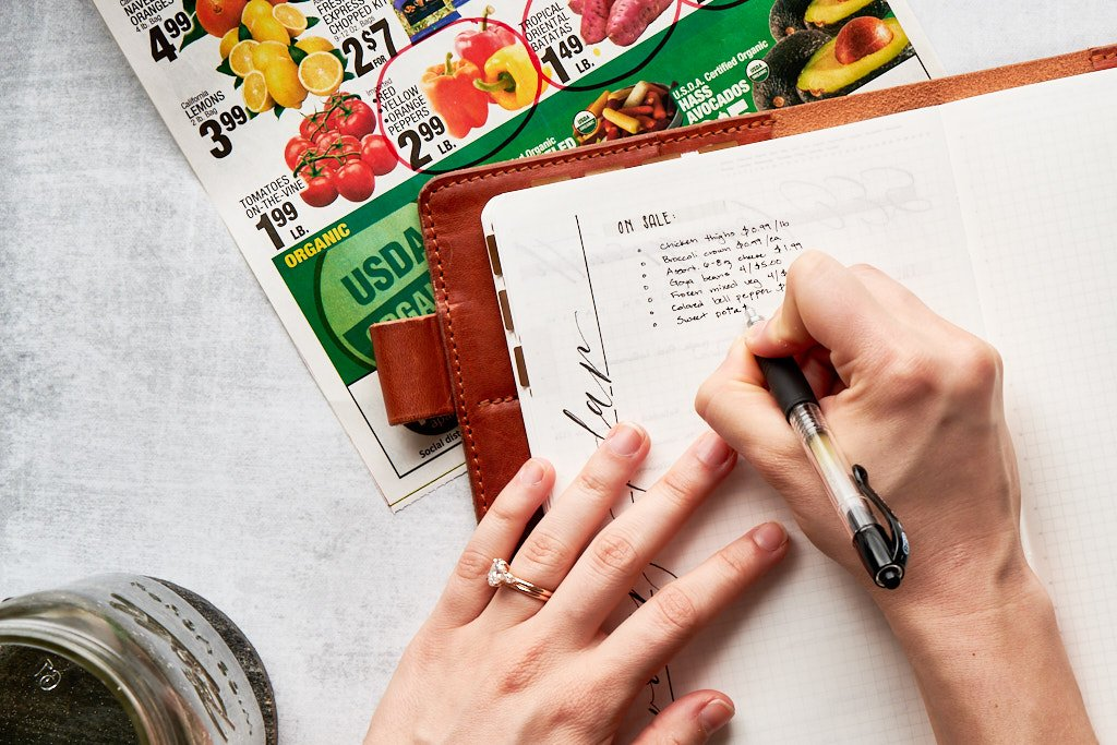 """A notebook sits on top of a grocery store sales flyer. The title of the page is obscured by two hands. One is writing items into a list called """"menu ideas"""""""