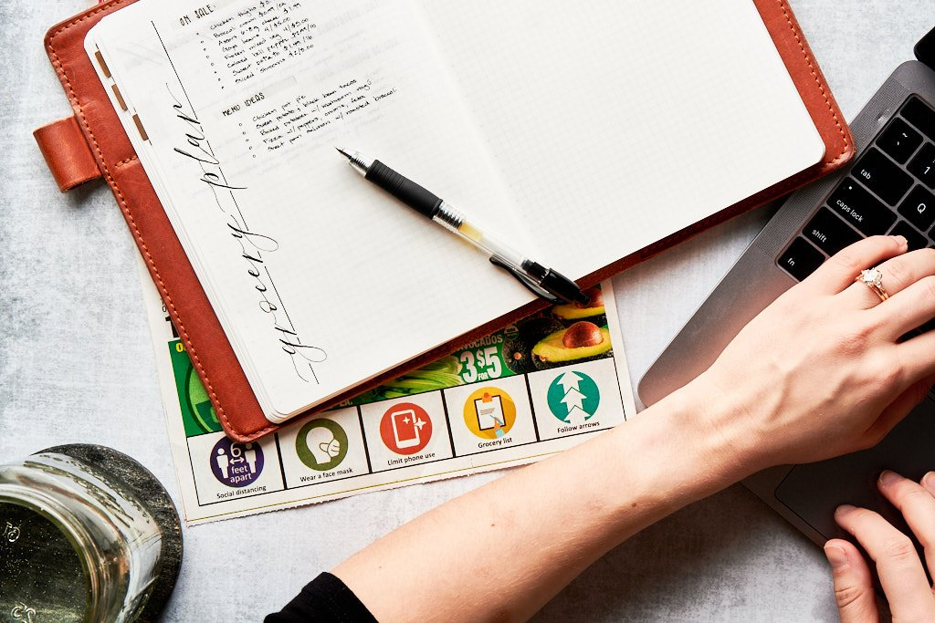"""An open notebook with a pen sitting on top of it. The pen is pointing to a section titled """"menu ideas"""" that has a few meals listed underneath. A hand sits on the keyboard of a laptop on the bottom right corner"""
