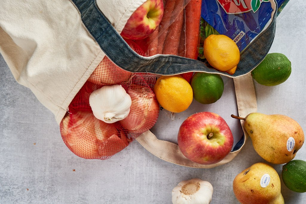 A bunch of produce items spilling out of a blue and white canvas bag. There are onions, bulbs of garlic, carrots, apples, pears, lemons and limes.