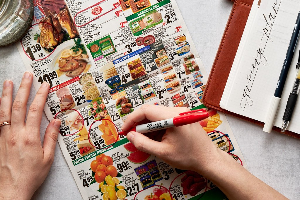 """A hand holding a red sharpie circles relevant sale items from a grocery store circular add. An open notebook that says """"grocery plan"""" sits to the right of the frame."""
