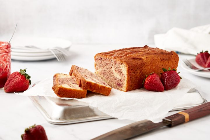 A loaf cake sits on a sheet of parchment paper on top of an upside-down quarter sheet pan. There are two slices of cake lying in front of the larger piece - the insides of the cake are swirled in pale yellow and purply-red. Strawberries are scattered around the frame, and a stack of plates sits in the background