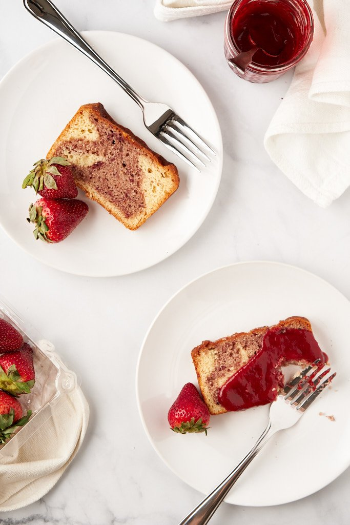 Two plates with slices of swirly strawberry cake. The slice in the bottom right corner is slathered in strawberry jam and has a bite taken out of it - a crumb-covered fork rests in the empty space.