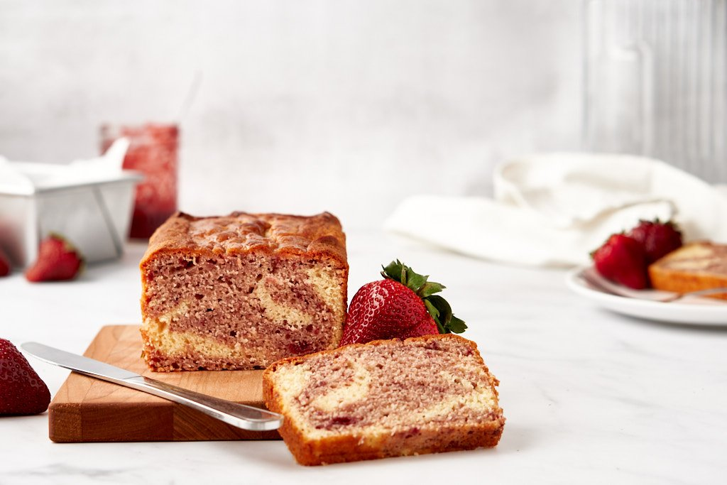 A cake sits on a cutting board in the lower right of the frame, so the swirled inside is facing you. A slice of the same cake leans against the edge of the board, and the knife used to cut the cake rests on the edge.