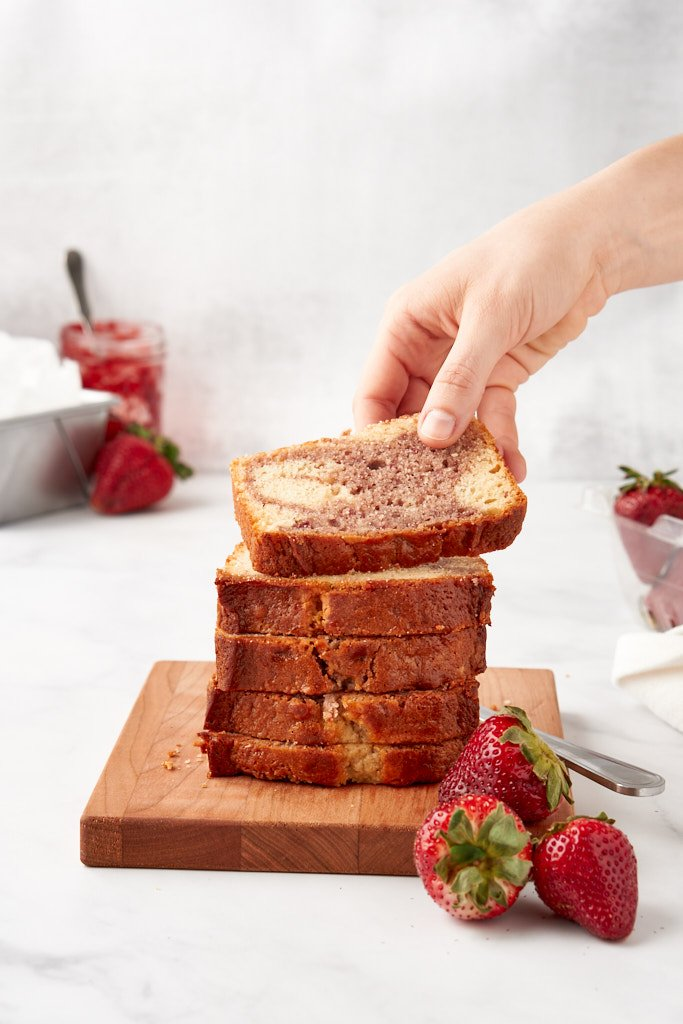 A hand reaches in from the top right of this vertical image to grab a slice of cake from a stack of slices sitting on a small cutting board. The slice of cake the hand is grabbing is angled towards the viewer so you can see the swirls.