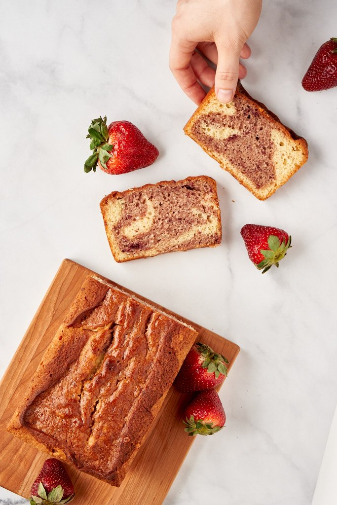 An overhead shot of a cake on a cutting board. Two slices are arranged on the tabletop in front of the cake so you can see the swirled insides - a hand is reaching for the slice closest to the top of the frame. Strawberries are scattered through the scene.