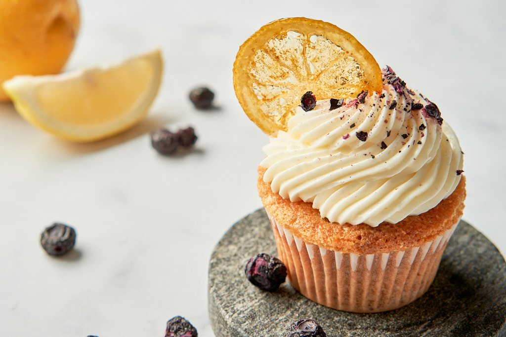 A single lemon-blueberry cupcake sits on a granite coaster to the right of the image. The cupcake is topped with a piped swirl of white frosting, and has a candied lemon round sticking out of the side, like a garnish on a cocktail glass. Crushed, dried blueberries are sprinkled on the frosting as decoration. A lemon and a few blueberries are scattered through the background
