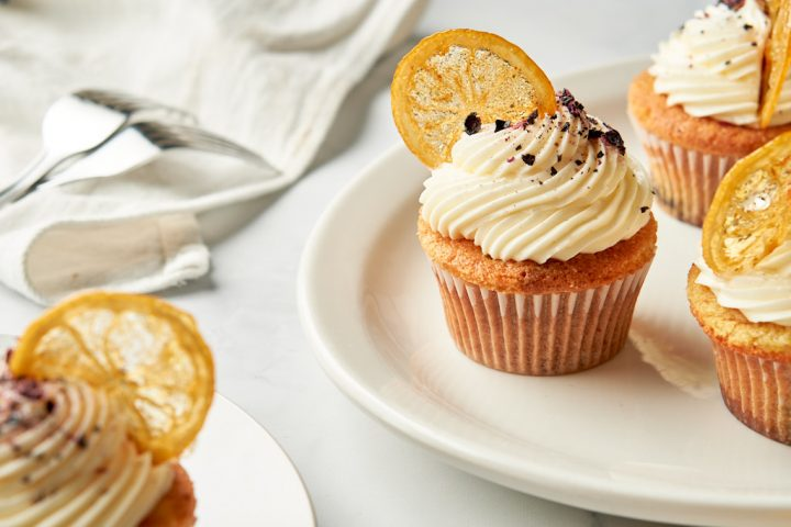A platter of cupcakes with a smaller plate with a single cupcake. The platter has three lemon-blueberry cupcakes on it - one is fully in frame, and the other two are slightly out of frame. Each cupcake has a round of candied lemon stuck into a swirl of piped frosting at a jaunty angle. Crushed freeze-dried blueberries top each cupcake like sprinkles.