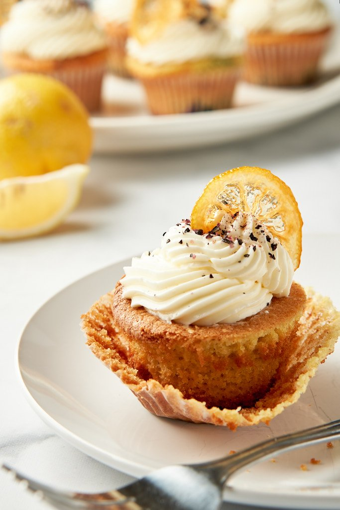 A single lemon-blueberry cupcake sits on a plate toward the bottom of the frame. The paper has been peeled back around all the sides and a fork is sitting in front of it, as if someone was prepared to start eating, but was interrupted. Behind the plate, and out of focus, there is a platter of cupcakes and a slice of lemon just visible.