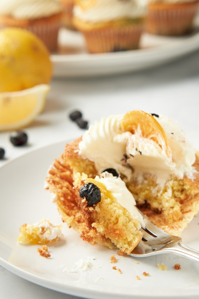 A partially-eaten cupcake sits on a plate at the bottom of the frame. A fork with a bite of cupcake balanced on it sits in front. The bite contains cake, frosting, and just a peek of lemon curd, topped with a blueberry. The platter of cupcakes is just visible behind the plate.