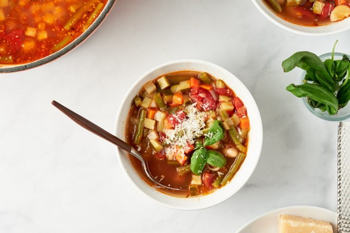 A bowl of vegetable minestrone in the center off the frame. A spoon rests in the bowl, as if someone was about to take a bite, but put the spoon down as they were distracted. The soup is garnished with basil and grated parmesan. You can just see the pot of soup in the top left corner of the frame, and there is a small bowl of basil leaves and a cheese grater in the bottom right.