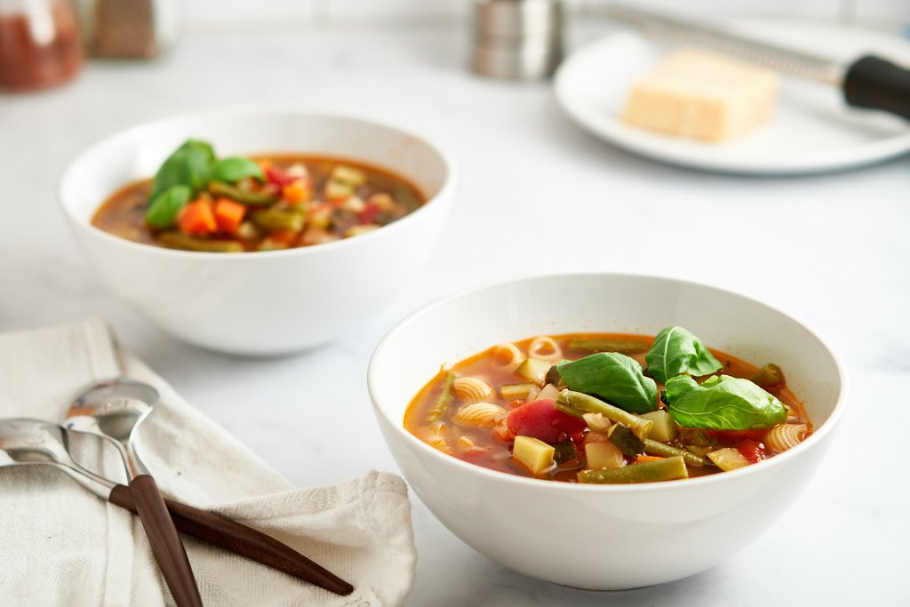 A 3/4 view of two bowls of vegetable soup. Each is garnished with 3 leaves of basil - you can see the light shining through the basil leaves. You can see a pepper grinder and a plate with cheese out of focus in the background